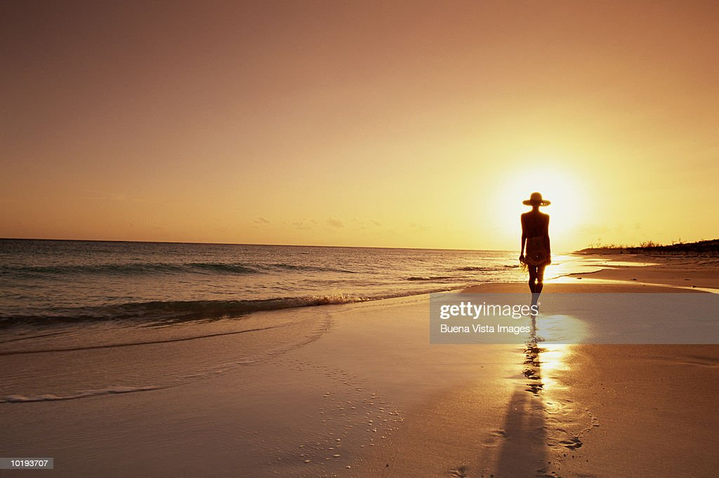 Woman walking on beach, sunset : Stock Photo