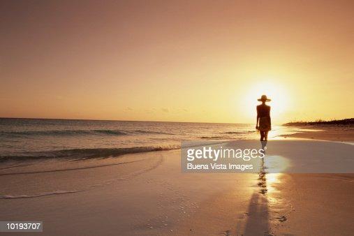 Woman walking on beach, sunset : Stock Photo