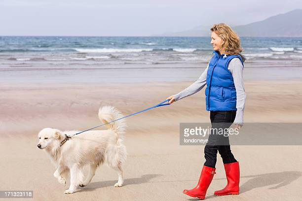 Woman Walking On Beach With Her Dog