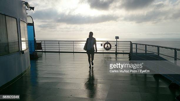 Woman Walking On Boat Deck Against Cloudy Sky