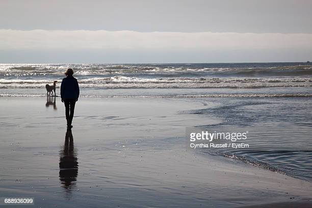 Woman Walking On Calm Beach Against Sky