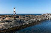 Woman walking on cliff, Sweden