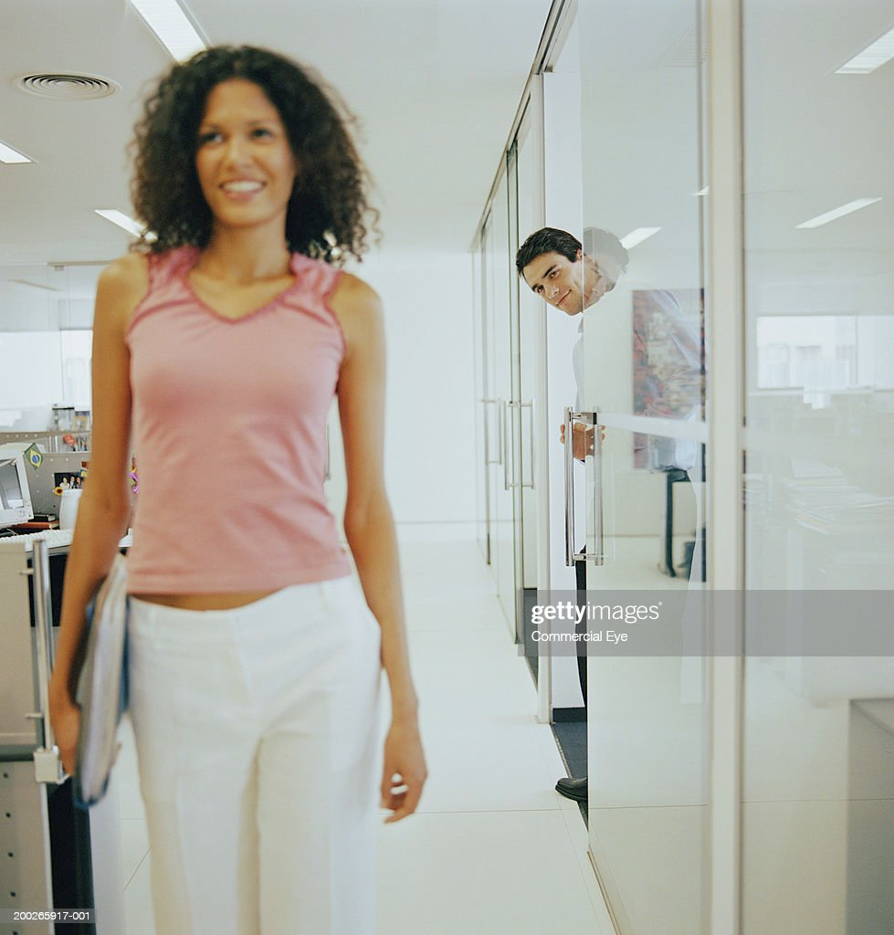 Woman walking on corridor, man peering from behind (focus on man) : Stock Photo