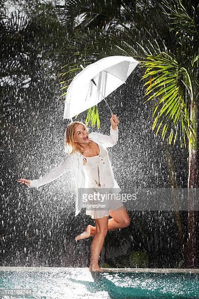Woman walking on edge of swimming pool during tropical rain