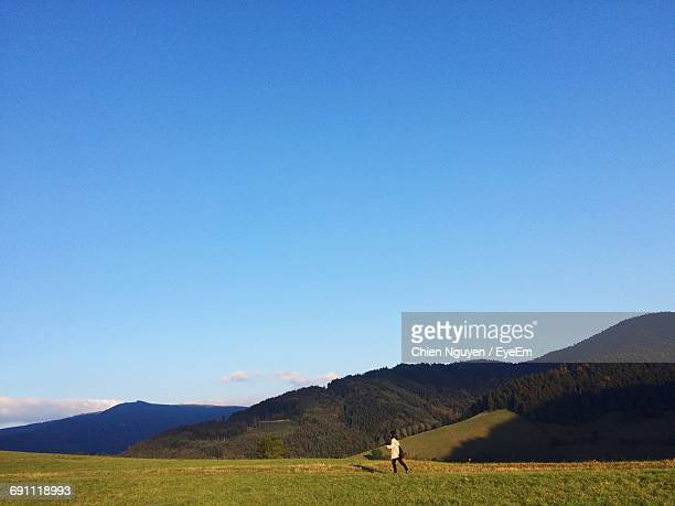 Woman Walking On Grassy Field By Mountains Against Sky