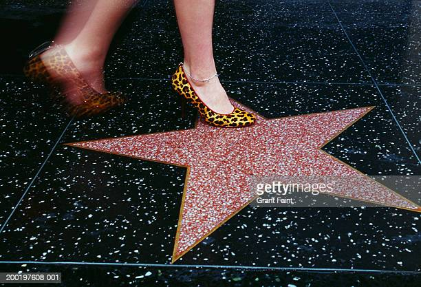 Woman walking on Hollywood Walk of Fame, low section (blurred motion)