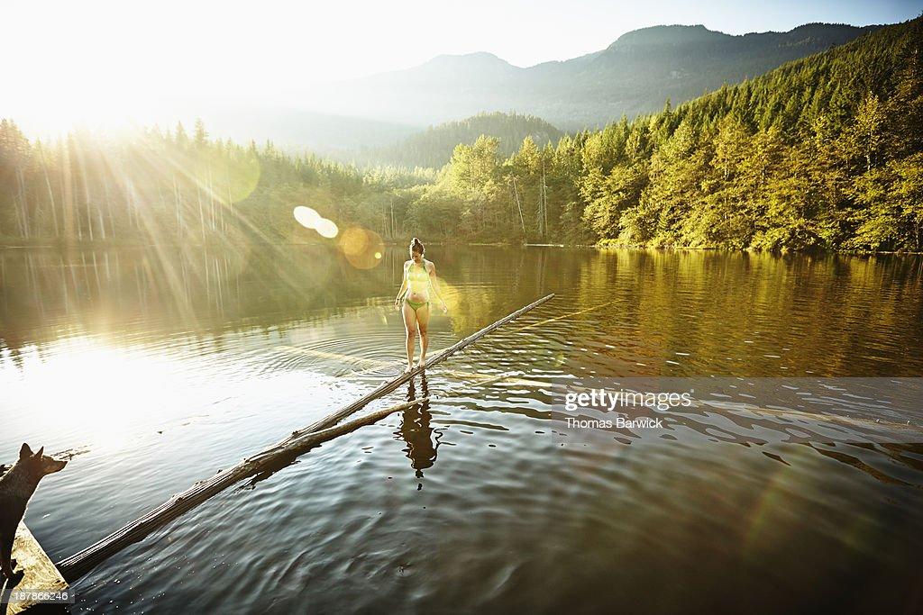Woman walking on log in alpine  lake : Stock Photo