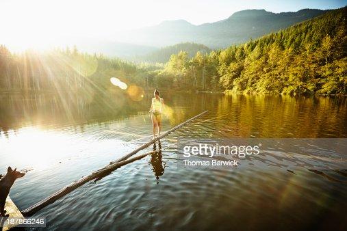Woman walking on log in alpine  lake