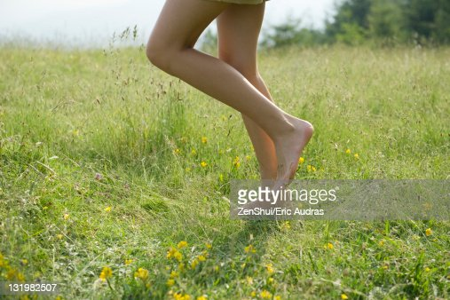 Woman walking on meadow with bare feet, low section