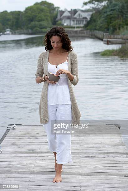 Woman walking on pier, holding bowl