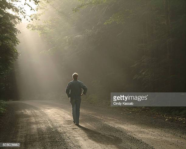 Woman Walking on Road in the Forest