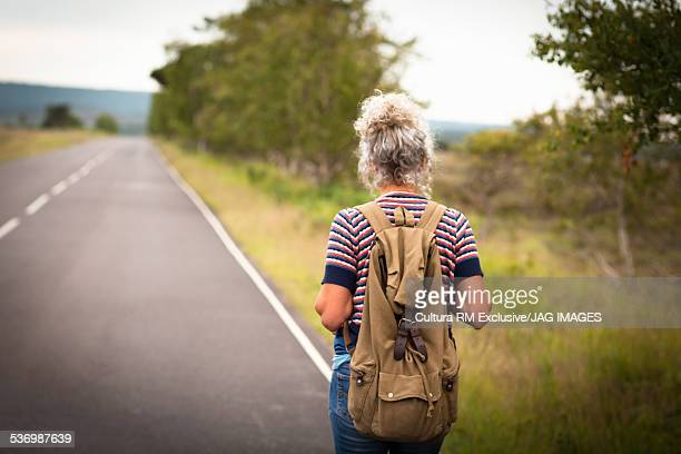 Woman walking on roadside, Studland, Dorset