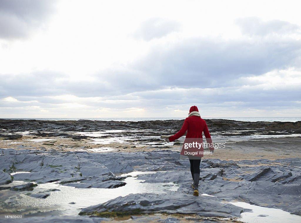 Woman walking on rocky coastline. : Stock Photo