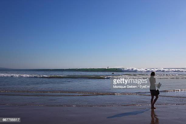 Woman Walking On Sea Shore Against Clear Sky During Sunset