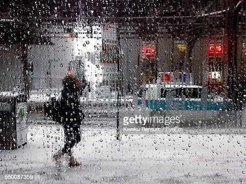 Woman Walking On Sidewalk During Rainy Season Seen Through Wet Glass Window