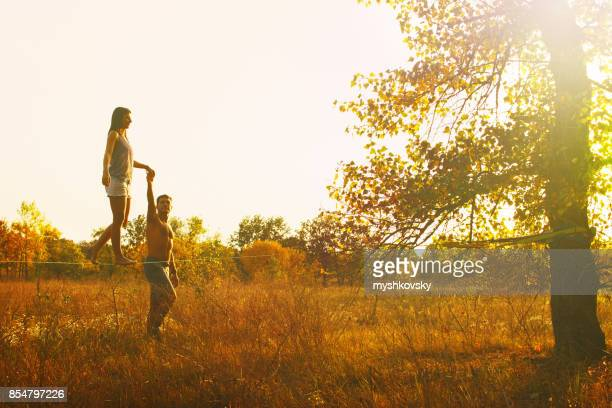 Woman walking on slackline in the meadow at sunset.