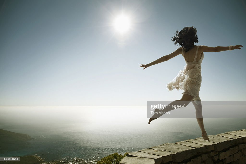 Woman walking on stone wall on cliff : Stock Photo