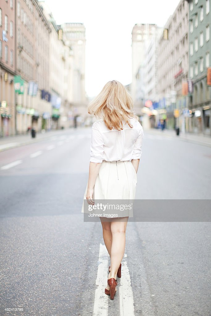 Woman walking on street, rear view