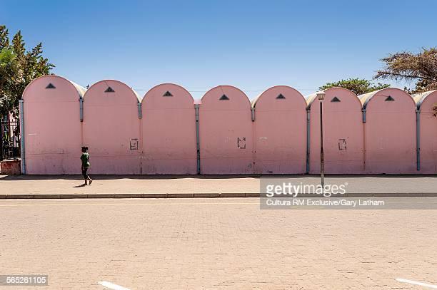 Woman walking on street with pink building, Katutura, Namibia, Namibia