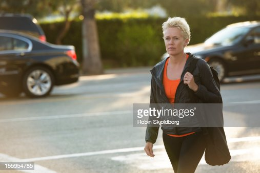 Woman walking on street with yoga mat : Stock Photo