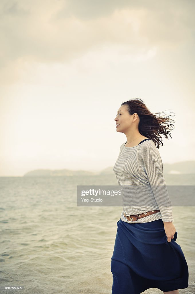 Woman walking on the beach : Stock Photo