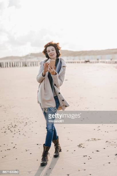 Woman walking on the beach with cell phone and headphones