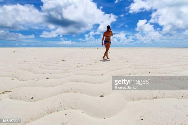 Woman walking on the long white beach at Kayangel Atoll, Palau