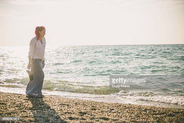 woman walking on the sand beach at golden hour