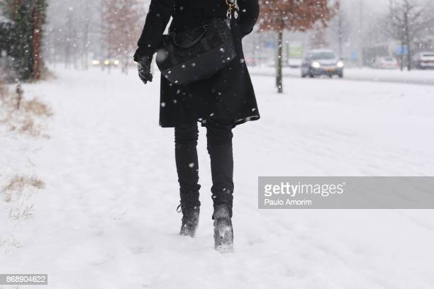 A woman walking on the street covered in snow