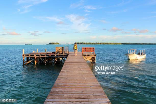 Woman walking on the wooden jetty during sunset, Carp Island, Palau