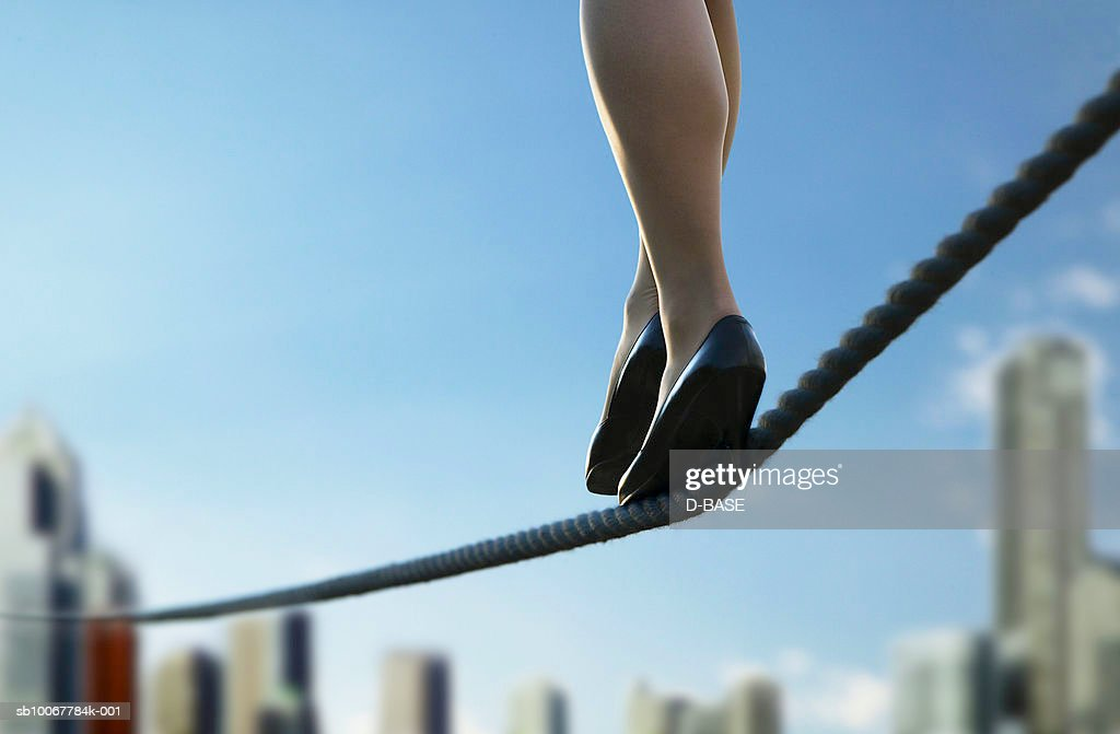 Woman walking on tightrope over cityscape, low section : Stock Photo