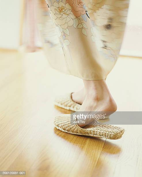 Woman walking on wood floor in woven slippers, low section