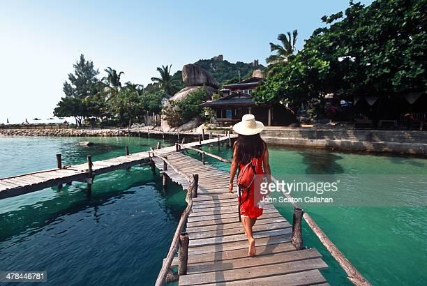 Woman walking on wooden pier.