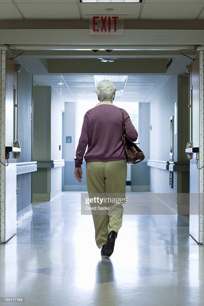 Woman walking out hospital exit : Stock Photo