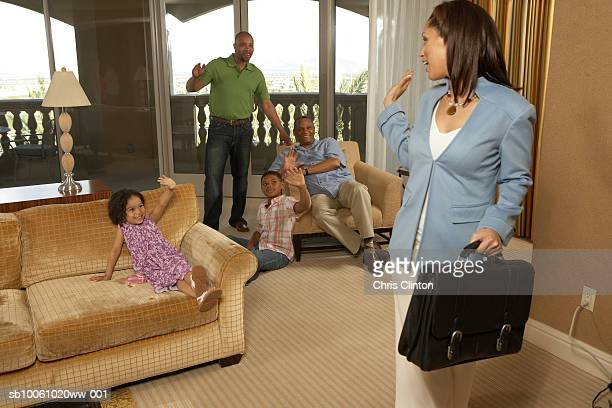 Woman walking out of room, leaving family including children (4-7), all waving hands