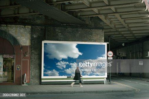 Woman walking past billboard poster of cloudy sky on city street