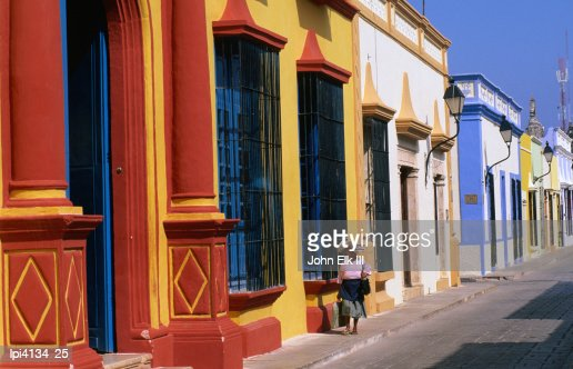 Woman walking past colourful house facades on street, Campeche, Mexico