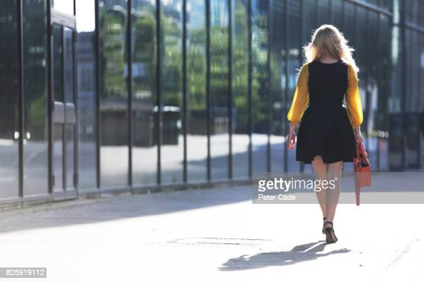 Woman walking past mirrored city building