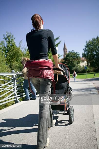Woman walking pram through picturesque city park