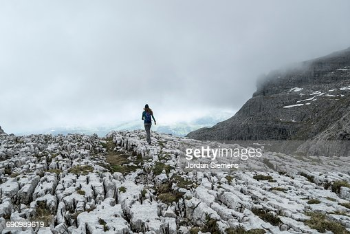 Woman walking rocky terrain