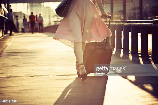 Woman walking sidewalk and carrying suitcase