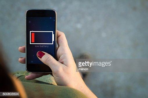 Woman walking smartphone low battery : Stock Photo
