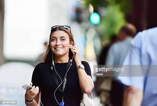 Woman, walking, talking, smiling, using mobile smart phone