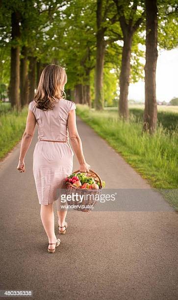 Woman walking through a park carrying a basket of vegetables