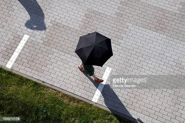 A woman walking through a plaza holding an umbrella