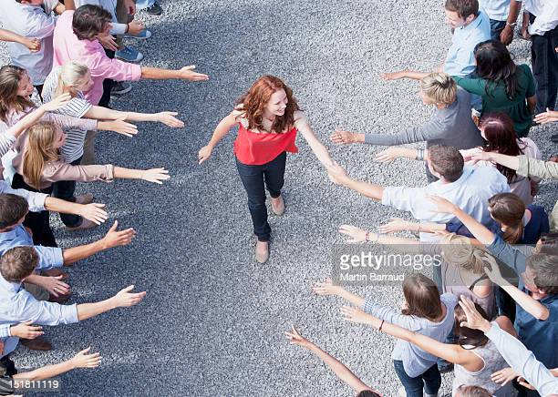 Woman walking through crowd with arms outstretched