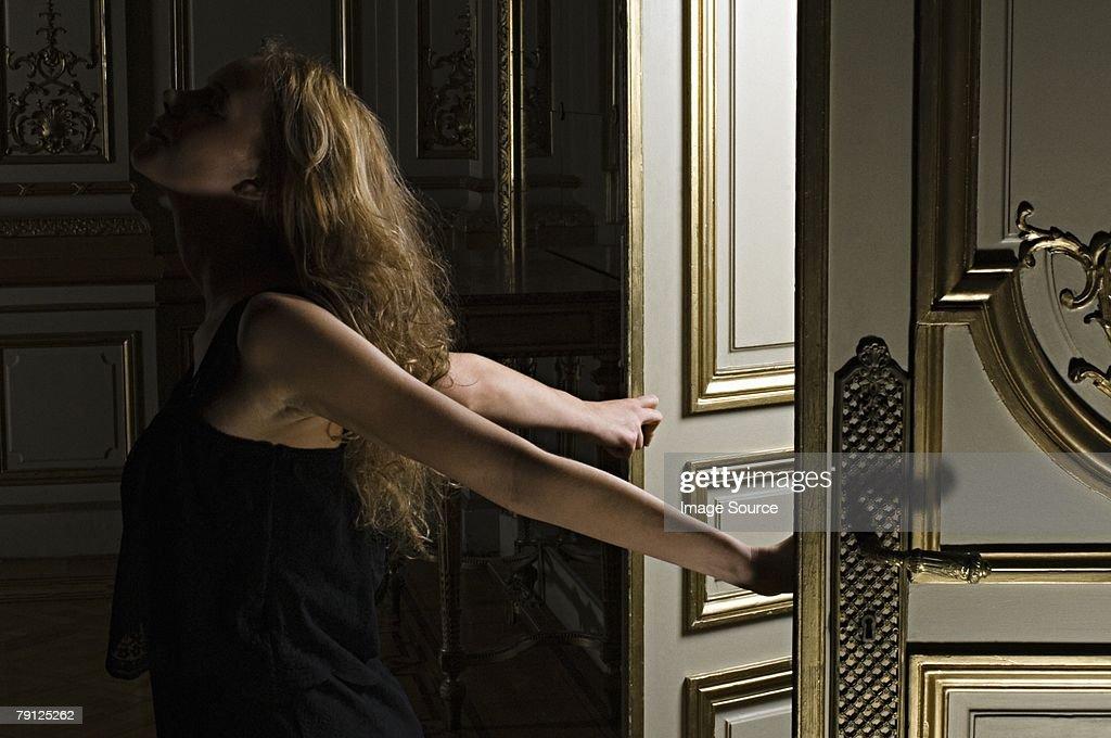 Woman walking through doors : Stock Photo