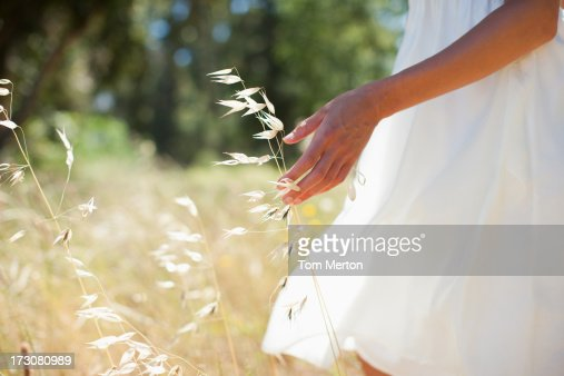 Woman walking through field : Stock Photo
