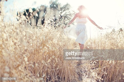 Woman walking through field touching grasses