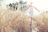 Woman walking through field touching grasses